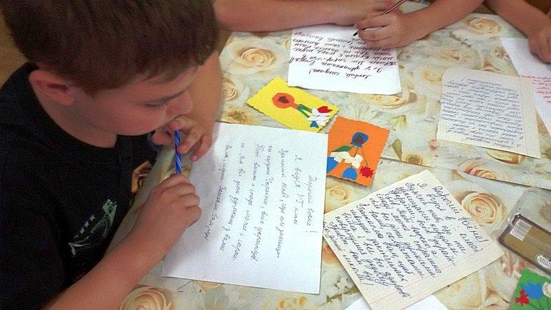 Маленький хлопчик пише листа захиснику Укра_ни