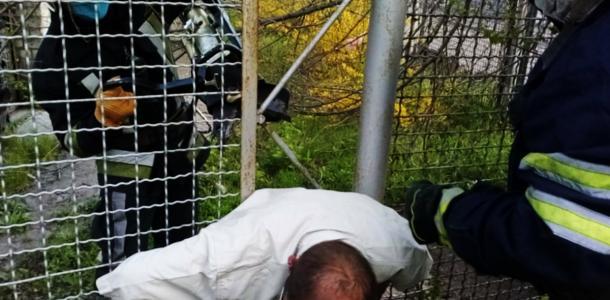 Попал в ловушку: спасатели вызволили мужчину, который застрял в заборе